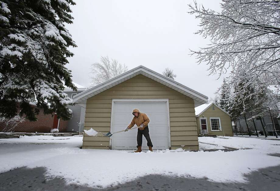 Gene Schmitz shovels heavy snow and slush from his driveway along Brighton Beach Road Monday, April 14, 2014, in Menasha, Wis. (AP Photo/The Post-Crescent, Dan Powers) NO SALES Photo: Dan Powers, Associated Press