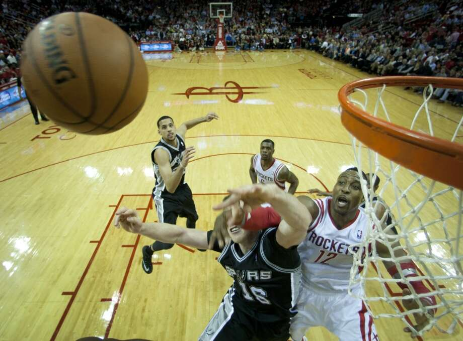 Spurs forward Aron Baynes (16) and Rockets center Dwight Howard (12) go after a loose ball. Photo: Brett Coomer, Houston Chronicle