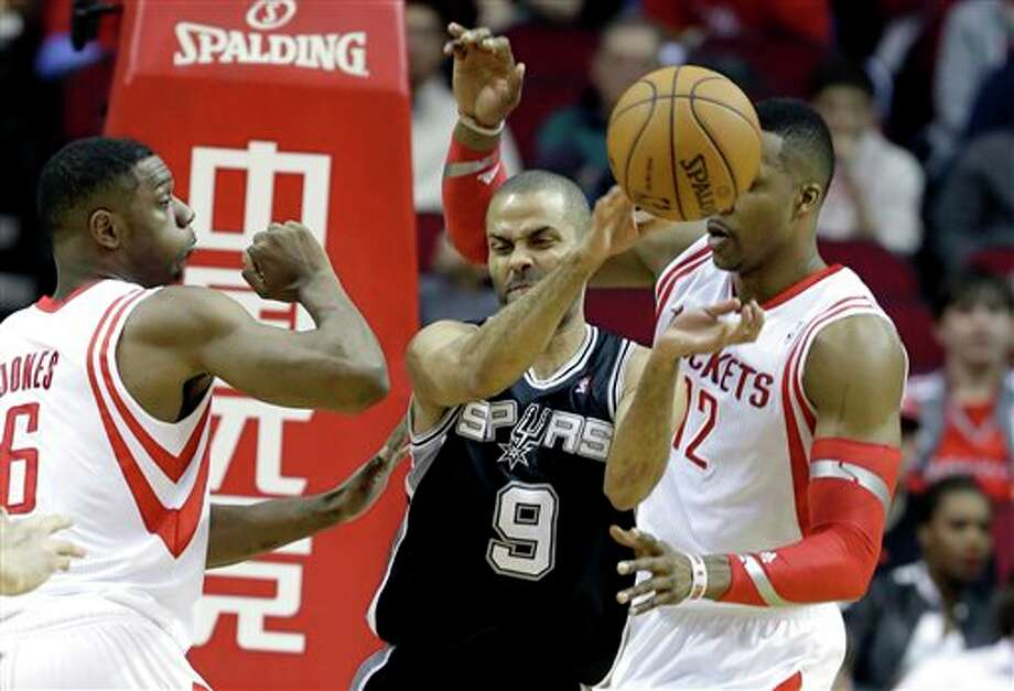 San Antonio Spurs' Tony Parker (9) passes the ball off under pressure from Houston Rockets Dwight Howard (12) and Terrence Jones (6) in the first half of an NBA basketball game Monday, April 14, 2014, in Houston. (AP Photo/Pat Sullivan) Photo: Pat Sullivan, AP / AP
