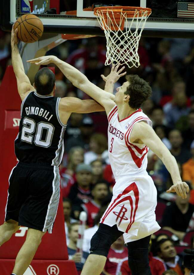 Rockets center Omer Asik, right, must figure that Spurs guard Manu Ginobili can't score if he can't see. The Rockets won Monday to complete a four-game season sweep against San Antonio. Photo: Brett Coomer, Staff / © 2014 Houston Chronicle