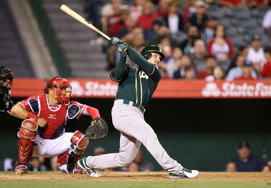 Pinch-hitter John Jaso smashes a two-run homer off the Angels' Ernesto Frieri in the ninth to give the A's a 3-2 lead. Photo: Stephen Dunn, Getty Images