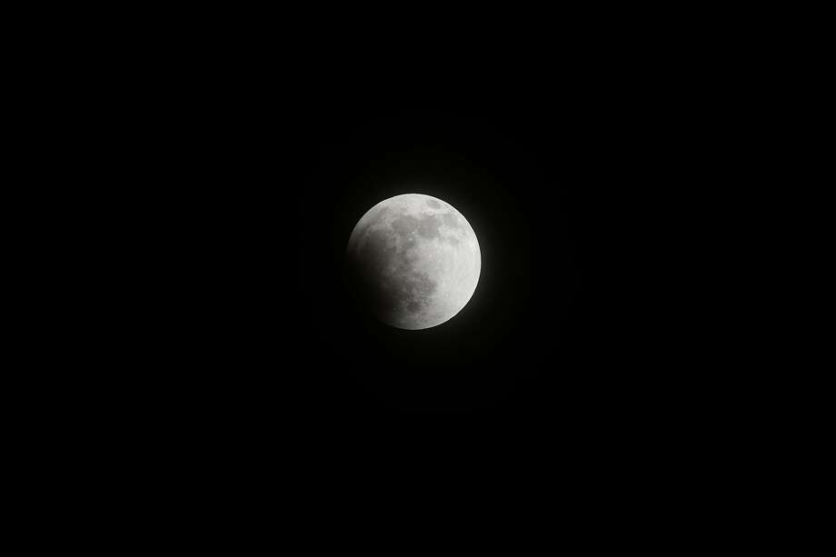 A lunar eclipse begins as seen from the San Gabriel Valley, east of downtown Los Angeles, on April 15, 2014.  The total lunar eclipse, visible from North and South America, started at 0706 GMT on April 15, and will last until 0824 GMT, the US space agency NASA said. Photo: Frederic J. Brown, AFP/Getty Images