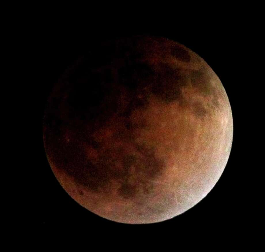 As the moon completely crosses the earth's shadow, the first of four total lunar eclipses, called the Blood Moon, occur in Whittier, Ca., USA on Tuesday, April 15, 2014. Photo: Nick Ut, Associated Press / AP