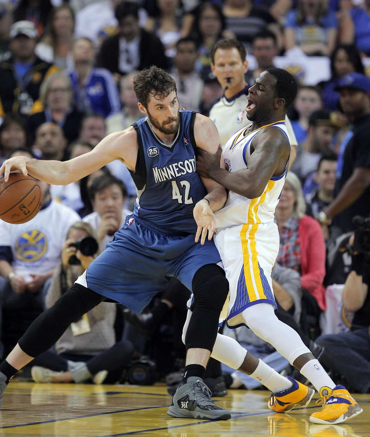 Kevin Love (42) drives to the basket against Draymond Green (23) in the first half. The Golden State Warriors played the Minnesota Timberwolves at Oracle Arena in Oakland, Calif., on Monday, April 14, 2014.