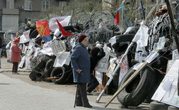 Women read banners as they pass the barricades of pro-Russian activists at a regional administration building that they had seized earlier in Donetsk, Ukraine, Tuesday, April 15, 2014.  Several government buildings have fallen to mobs of Moscow loyalists in recent days as unrest spreads across the east of the country. Photo: Efrem Lukatsky, AP / AP