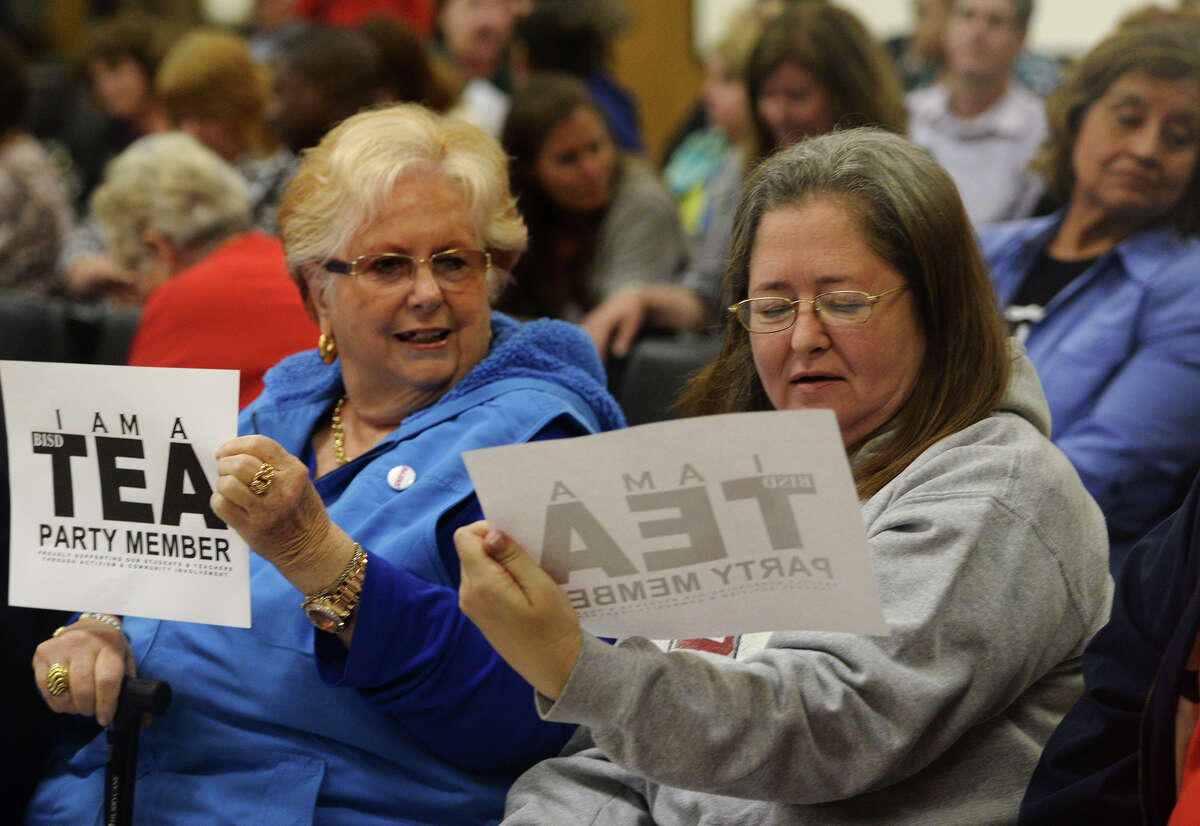 Dottie Carruth, left, holds a sign lauding the TEA's decision to remove the BISD board of trustees while Melanie Robertson reads the fine print before Monday's school board meeting. The Beaumont Independent School District held its monthly agenda review meeting Monday night. Monday morning, the TEA announced that it would be replacing the superintendent and the school board. Photo taken Monday, 4/14/14 Jake Daniels/@JakeD_in_SETX
