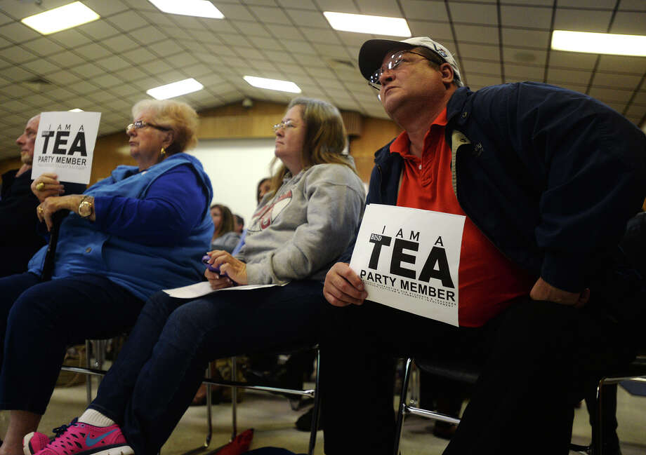 Dottie Carruth, left, and Danny McCurtain, right, hold signs praising TEA's decision to replace the BISD school board while they and Melanie Roberton, center, sit in on Monday night's board meeting. The Beaumont Independent School District held its monthly agenda review meeting Monday night. Monday morning, the TEA announced that it would be replacing the superintendent and the school board.