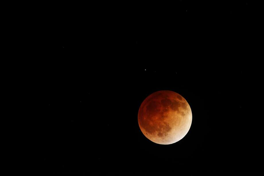 A lunar eclipse is seen in the early morning hours of April 15, 2014 from Panoramic Highway near the entrance to Mt. Tamalpais State Park in Mill Valley, Calif. Photo: Pete Kiehart, The Chronicle