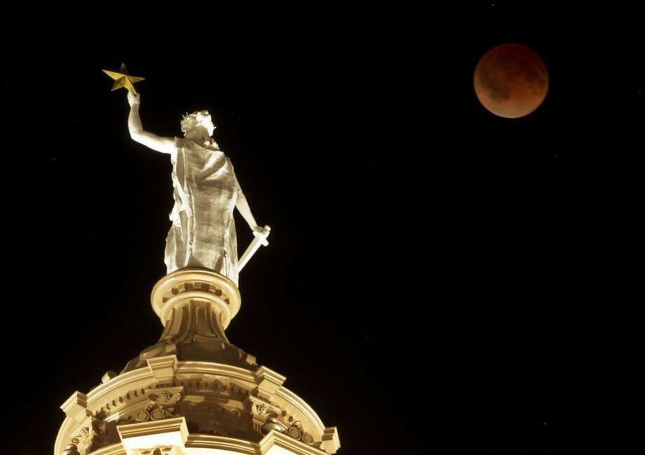 The moon turns red during a total lunar eclipse over the Goddess of Liberty statue atop the Capitol in Austin, Texas, at 3:23 a.m. CDT on Tuesday, April 15, 2014. Photo: Jay Janner, McClatchy-Tribune News Service