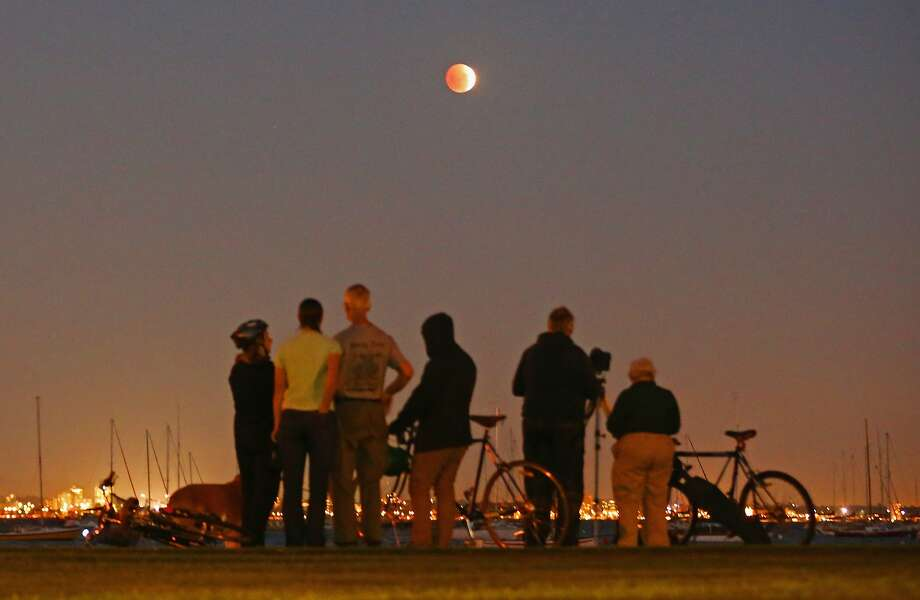 "People watch as the 'Blood Moon' rises over the water in Wlliamstown on April 15, 2014 in Melbourne, Australia. The Lunar Eclipse, resulting in the Moon appearing to be an orange-red colour is due to a perfect alignment of the Sun, Earth and Moon, otherwise known as ""syzygy"". Photo: Scott Barbour, Getty Images"