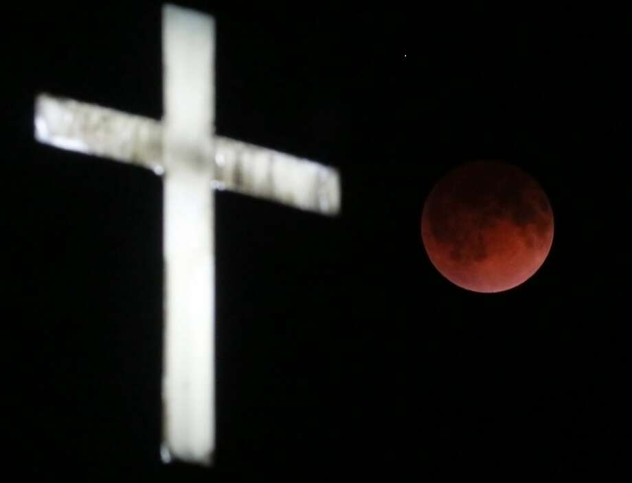 The Earth's shadow renders the moon in a crimson hue during a total lunar eclipse behind the illuminated steeple of St. Olaf Lutheran Church in the town of Ashippun , Wis. Tuesday, April 15, 2014. Photo: John Hart, Associated Press