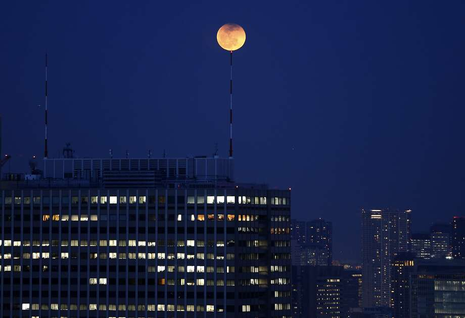 The partial lunar eclipse is seen atop an antenna installed on the roof of a high-rise building in Tokyo April 15, 2014. The lunar eclipse on Tuesday will unfold over three hours when the moon begins moving into Earth's shadow Photo: Issei Kato, Reuters