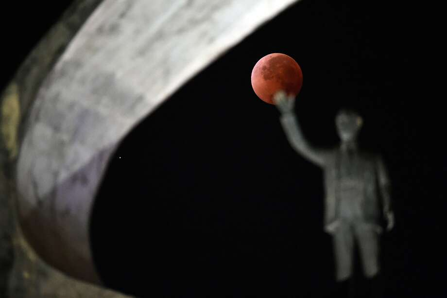 This picture taken on April 15, 2014 shows the moon during a total lunar eclipse over the Juscelino Kubitschek Memorial in Brasilia. The entire event was to be visible from North and South America, but sky watchers in northern and and eastern Europe, eastern Africa, the Middle East and Central Asia were out of luck, according to US space agency NASA. Photo: Evaristo Sa, AFP/Getty Images