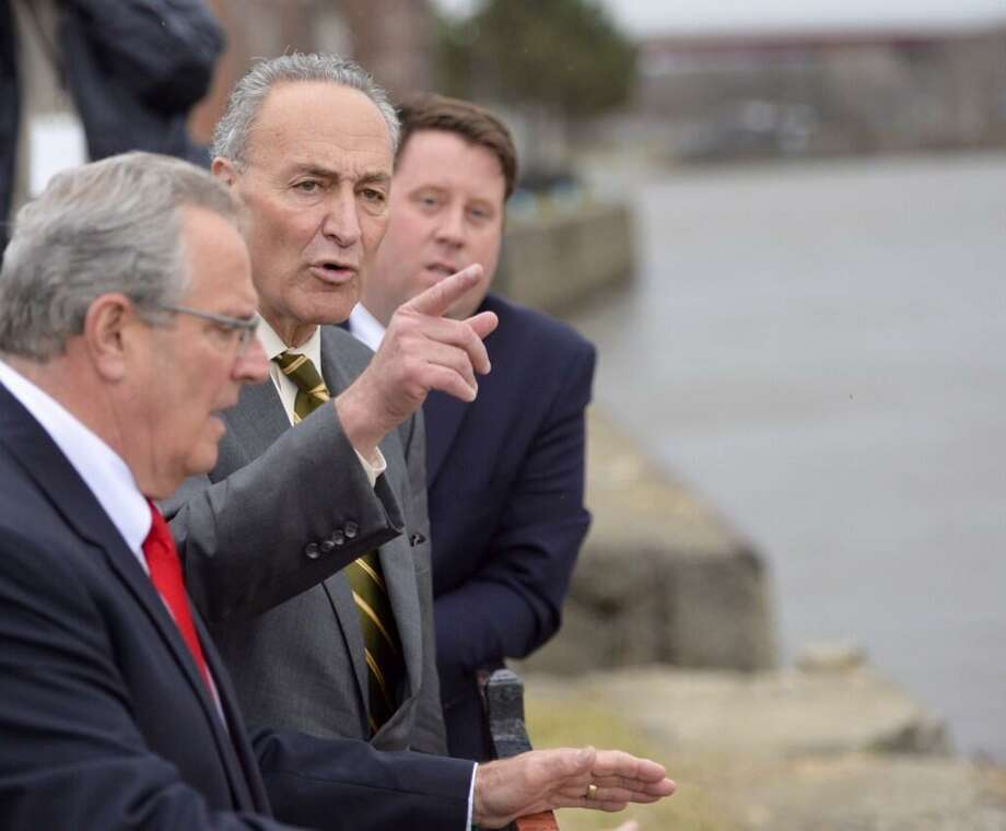 Sen. Charles Schumer, center, with Tom Nardacci, right, of Troy BID and Mayor Lou Rosamilia, left, checks the seawall deterioration in Troy. (Skip Dickstein/Times Union)