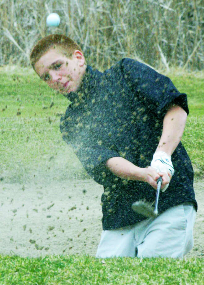 The Green Wave's John Pace blasts his way out of a sand trap during practice at Candlewood Valley Country Club for the New Milford High School golf season. April 2014 Photo: Norm Cummings / The News-Times