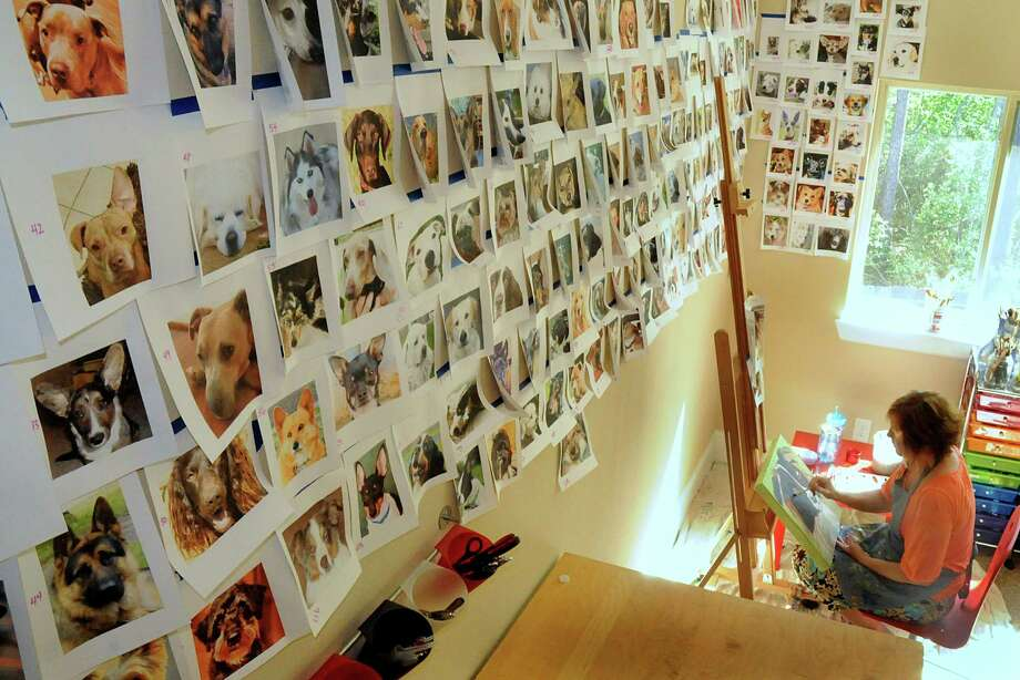 Artist Leiann Klein paints a dog's portrait at her home studio, surrounded by numbered dog photographs on the wall from emails sent to her by owners who submitted their rescued dogs. She chooses one photo a day to paint and will do so through May 10. Photo: David Hopper, Freelance / freelance