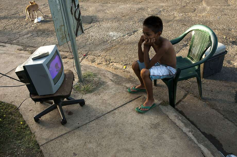 Shaken and stirred: A boy watches TV in the street in Managua because he's too afraid to go inside his house.