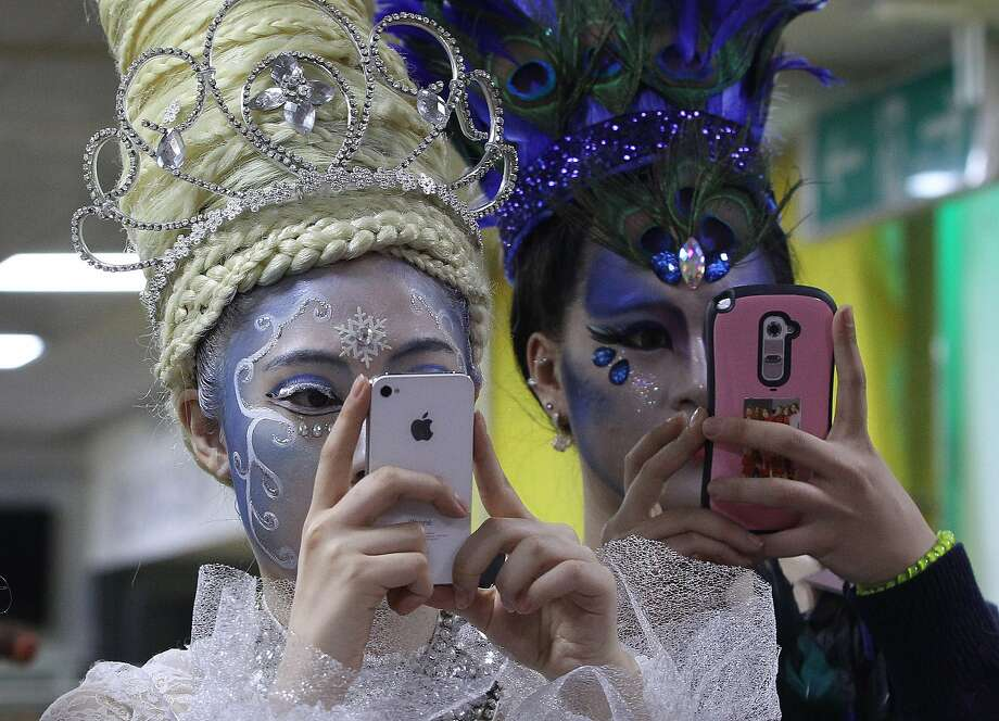 You guys look so ridiculous, we have to take your picture:Models snap photos of their colleagues (not shown) during the K-Beauty World Fashion Festival in Gwacheon, South Korea. About 15,000 makeup artists, hairdressers and fashion designers from 56 countries participated in the annual event to promote Korean culture. Photo: Ahn Young-joon, Associated Press