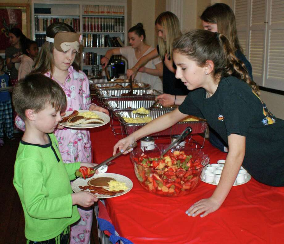 Jackson Dooley and Vivi Reeves line up for dinner (or is it breakfast?) served by Nichole LaBadie during the First Presbyterian Church's third annual PJ's and Pancakes event. Photo: Contributed Photo, Contributed / New Canaan News Contributed