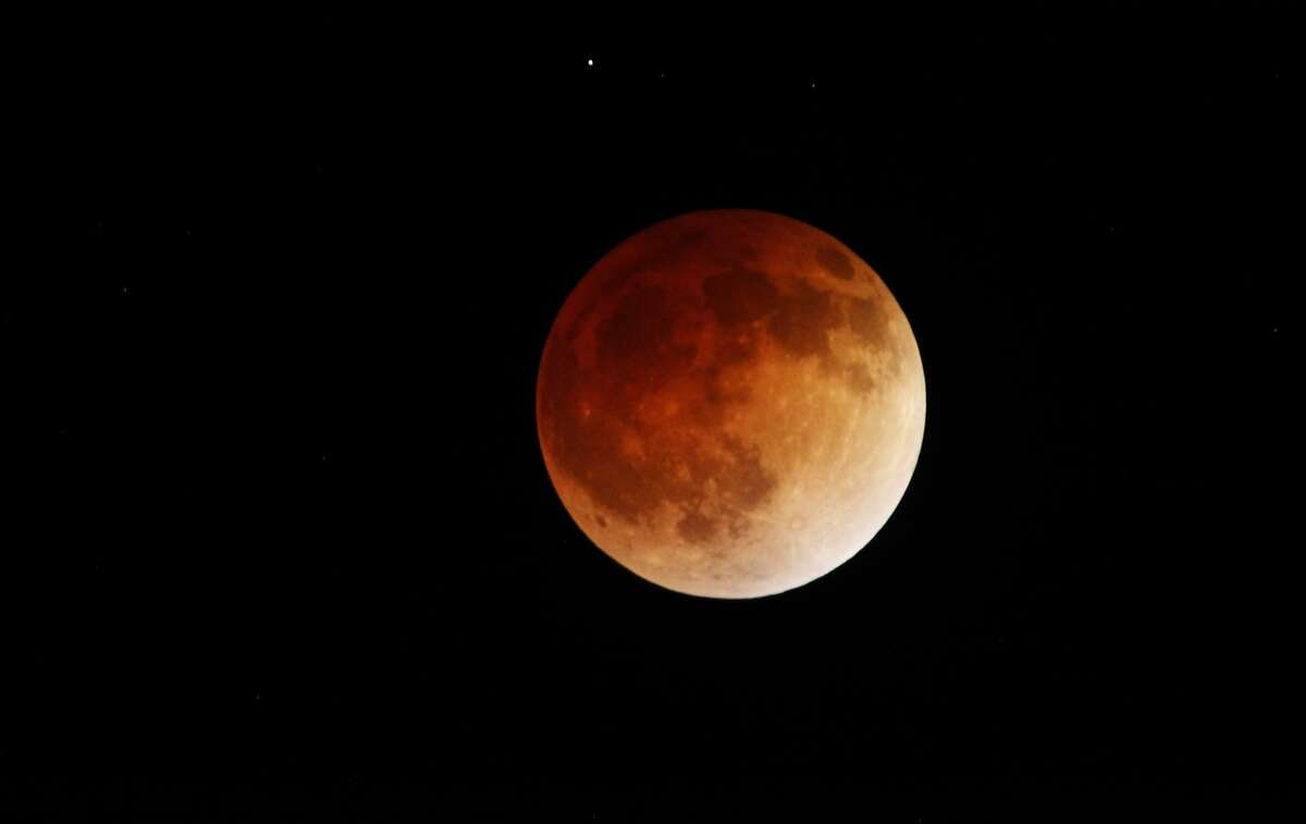 A lunar eclipse is seen in the early morning hours of April 15, 2014 from Panoramic Highway near the entrance to Mt. Tamalpais State Park in Mill Valley, Calif.