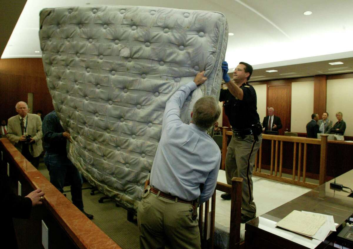 """Harris County Sheriff's Dept. detectives assist bailiff J. L. Morin assemble the Wright murder bed, 03/03/04 in Judge Jim Wallace's 263rd District Court in the Criminal Justice Center. The bed was assembled for photographs to be taken and entered in the evidence file so that the bed could be gotten """"rid of"""". Susan Wright was later found guilty of murdering her husband Jeffrey Wright by stabbing him 192 times while tied to the bed. (Buster Dean/ Chronicle)"""