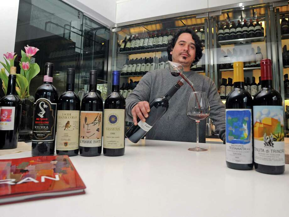 David Corbo, one of the owners of Golden View Firenze, pours Karan, Brunello di Montalcino, one of their wines bottled and labeled privately for the restaurant on Railroad Avenue in Greenwich, Conn. Photo: Cathy Zuraw / Greenwich Time