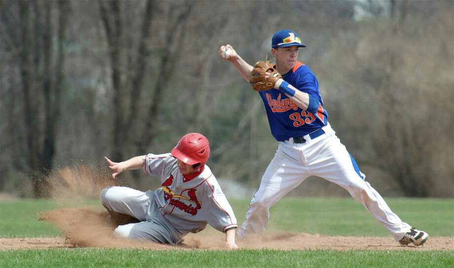 Danbury's Eric Cerno, #33, goes to throw to first to try for the double play as Carlos Fernandez, #14, of Greenwich,slides into second during an FCIAC boys baseball game between Greenwich High School and Danbury High School on Monday, April 14, 2014, in Danbury, Conn. Photo: H John Voorhees III / The News-Times Freelance