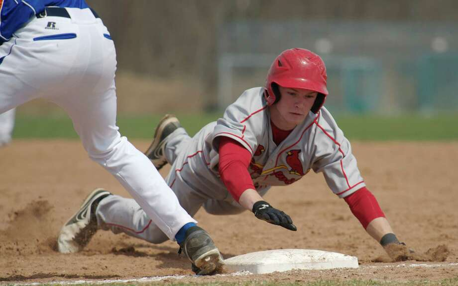 The Cardinal's Devin McGrath, #5, dives safely back to first to avoid a pick off during a boys FCIAC baseball game between Greenwich High School and Danbury High School, on Monday, April 14, 2014, in Danbury, Conn. Danbury's Lenny Rodriguez, #31, is playing first base. Photo: H John Voorhees III / The News-Times Freelance