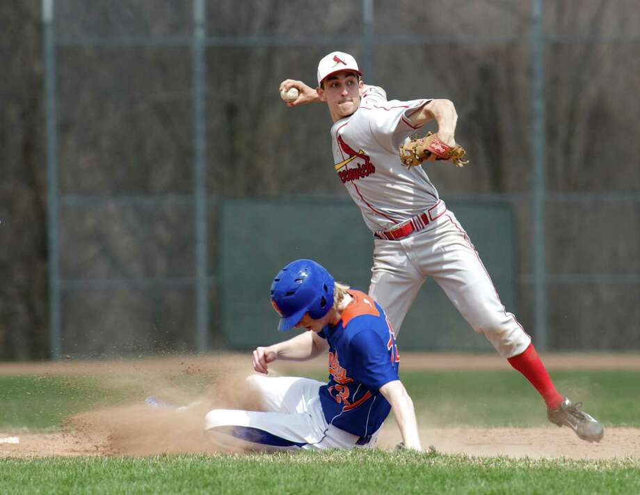 Danbury's Corey Brosz, #13, slides into second as James Hintzen, #21, of Greenwich,  throws to first to try for the double play, during an FCIAC boys baseball game between Greenwich High School and Danbury High School on Monday, April 14, 2014, in Danbury, Conn. Photo: H John Voorhees III / The News-Times Freelance