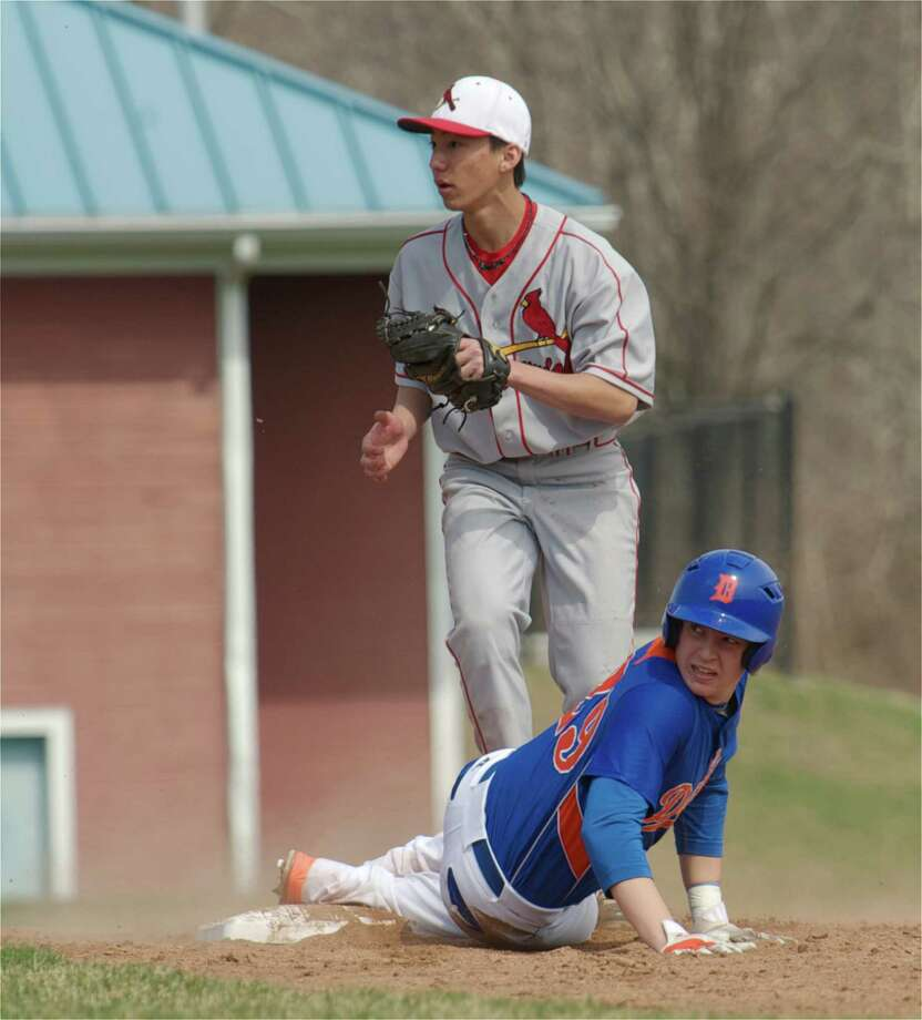 Keigo Fujikura, #10, of Greenwich, and Danbury's Dan Clancy, #29, look up to see the call after Clancy slide into second base during a FCIAC boys baseball game on Monday, April 14, 2014, between Greenwich High School and Danbury High School,  in Danbury, Conn. Clancy was out at second. Photo: H John Voorhees III / The News-Times Freelance