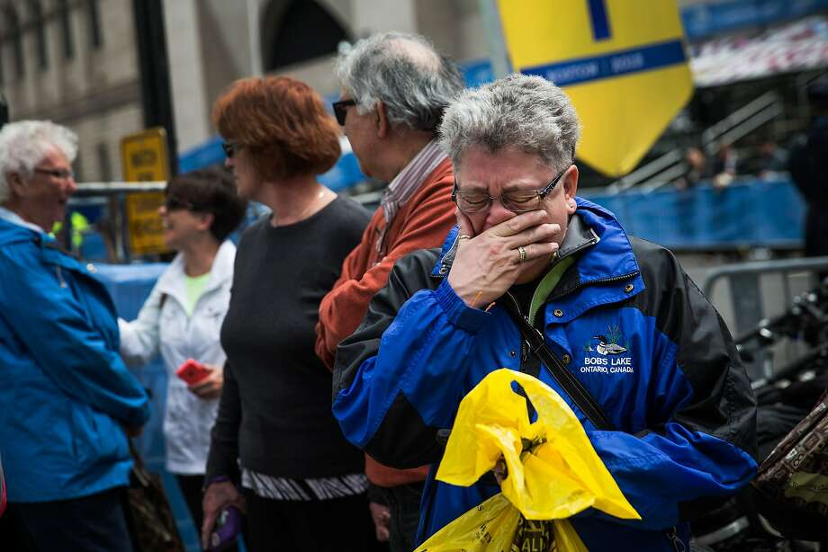 Sharon Neary of Rochester, N.Y., cries while watching the ceremony marking the anniversary of the Boston Marathon bombing on a large outdoor screen. Neary was standing near the bombs when they went off last April 15 in a crowd of people near the finish line of the marathon. Photo: Andrew Burton, Getty Images