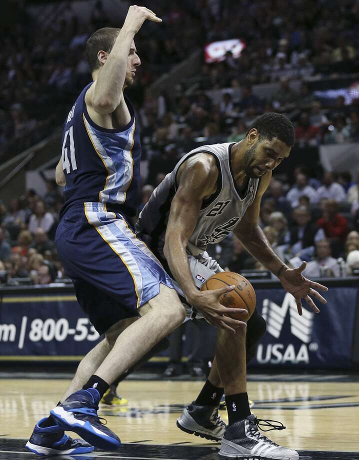 San Antonio Spurs' Tim Duncan tries to control the ball as Memphis Grizzlies' Kosta Koufos defends during the second half at the AT&T Center, Sunday, April 6, 2014. The Spurs won 112-92. Photo: Jerry Lara, San Antonio Express-News