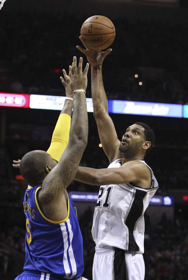 Spurs' Tim Duncan (21) shoots over Golden State Warriors' Marreese Speights (05) in the first half at the AT&T Center on Wednesday, Apr. 2, 2014. Photo: Kin Man Hui, San Antonio Express-News