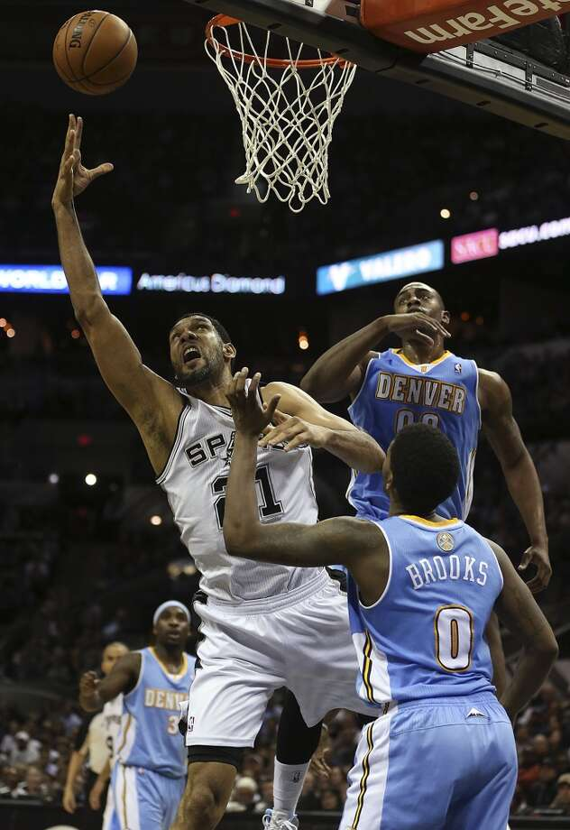San Antonio Spurs' Tim Duncan goes for two between the defense of Denver Nuggets' Aaron Brooks and Darrell Arthur during the second half at the AT&T Center, Wednesday, March 26, 2014. The Spurs won 108-103. Photo: Jerry Lara, San Antonio Express-News