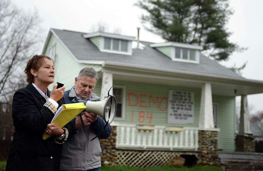 Melanie Marks, of Fairfield, and Edwards Collins, of Milford, protest the demolition of the former home of aviation pioneer Gustave Whitehead Tuesday, April 15, 2014, outside the house on Alvin Street in Fairfield, Conn. Photo: Autumn Driscoll / Connecticut Post