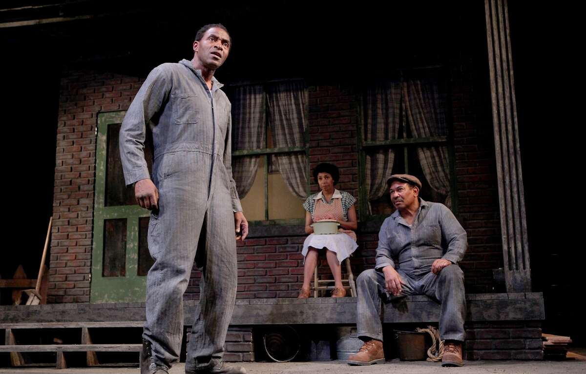 """Troy Maxson (Carl Lumbly, left) and fellow garbageman Jim Bono (Steven Anthony Jones) discuss a confrontation as Troy's wife Rose (Margo Hall) listens in August Wilson's """"Fences"""" at Marin Theatre Company."""