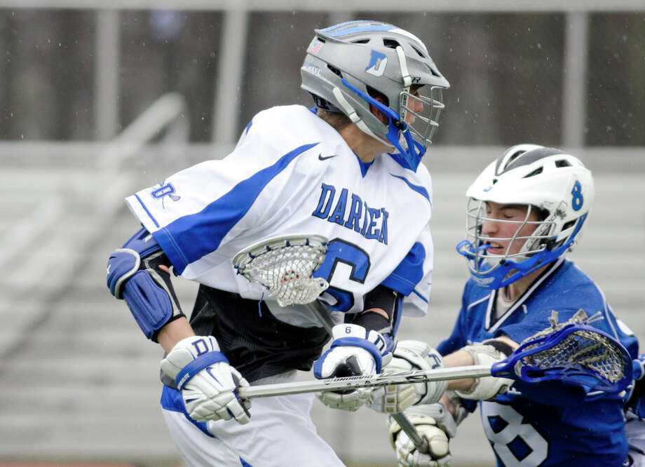 Darien's Peter Lindley (6) carries the ball as Fairfield Ludlowe's Brett Dammeyer (8) defends during the boys lacrosse game at Darien High School on Tuesday, Apr. 15, 2014. Photo: Amy Mortensen / Connecticut Post Freelance