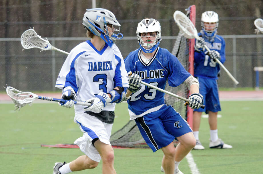 Darien's Colin Minicus (3) carries the ball as Fairfield Ludlowe's Mitch Wycoff (23) defends during the boys lacrosse game at Darien High School on Tuesday, Apr. 15, 2014. Photo: Amy Mortensen / Connecticut Post Freelance
