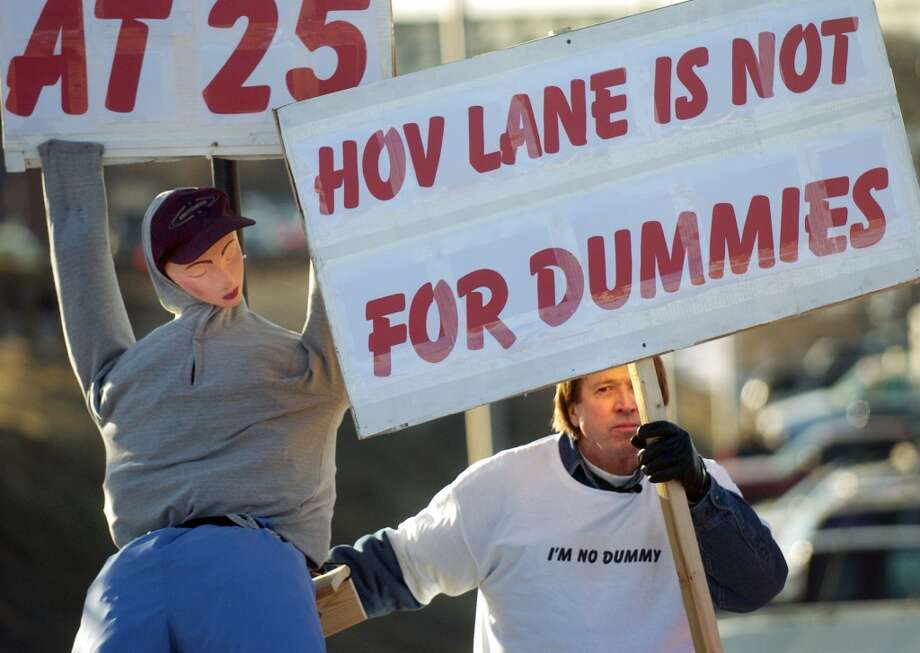 """Greg Pringle and his makeshift mannequin, which he named Tillie, attract the attention of motorists on the on-ramp to eastbound U.S. Highway 36 from Sheridan Boulevard with a sign stating """"The HOV Lane is not for Dummies,"""" Tuesday, March 14, 2006, in Westminster, Colo. Pringle was doing this to complete a sentence handed down two weeks ago by a Westminster judge for driving in the high occupancy vehicle lane on his own with Tillie as his """"passenger."""" A makeshift mannequin that failed to fool police monitoring the high-occupancy vehicle lane on Highway 36 fetched $15,000 in an auction on eBay, with proceeds going to charity, the buyer announced Friday March 24, 2006. Denver-based Video Professor bought the Styrofoam head, coat hanger, and clothing stuffed with newspapers from HOV scofflaw Greg Pringle, 53, of Broomfield, said Brian Olson, a company spokesman.   (AP Photo/Denver Post, Glenn Asakawa) Photo: GLENN ASAKAWA, AP"""