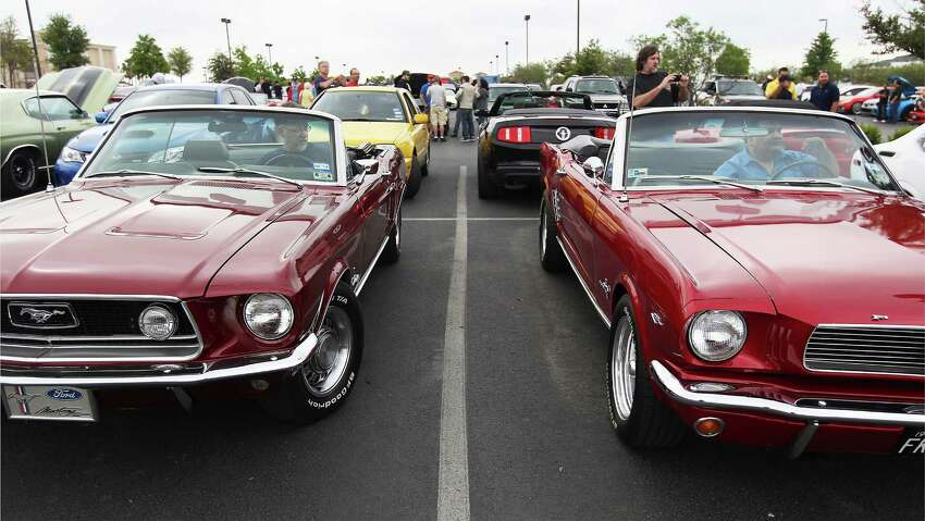 Owners Mark Plested (left) and Steve Garcia sit in their vintage Ford Mustings that were on display during a gathering at the Cars and Coffee event on Saturday, Apr. 12, 2014. The ubiquitous Mustang and its owners will be celebrating the 50th anniversary this month.