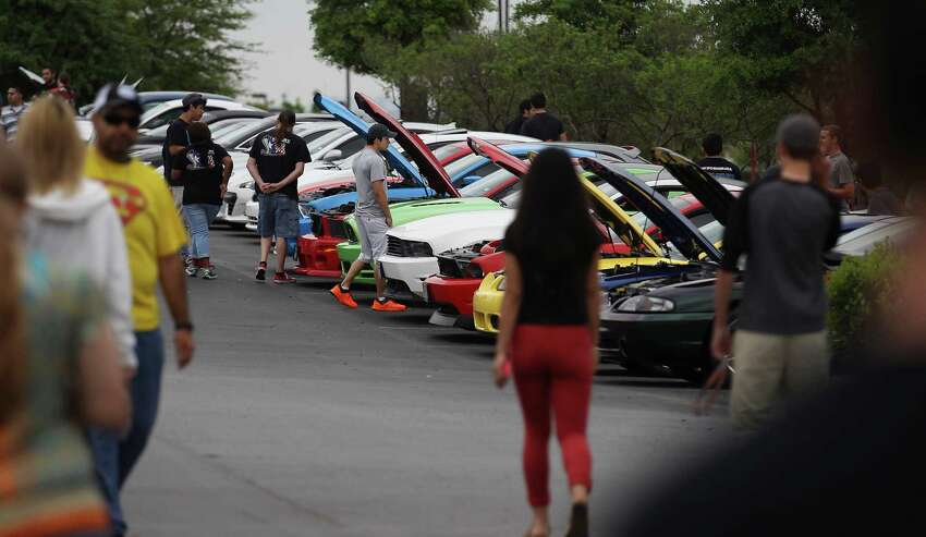 Car enthusiasts walk past a row of Ford Mustangs at a gathering at the Cars and Coffee event on Saturday, Apr. 12, 2014. The ubiquitous Mustang and its owners will be celebrating the 50th anniversary this month.