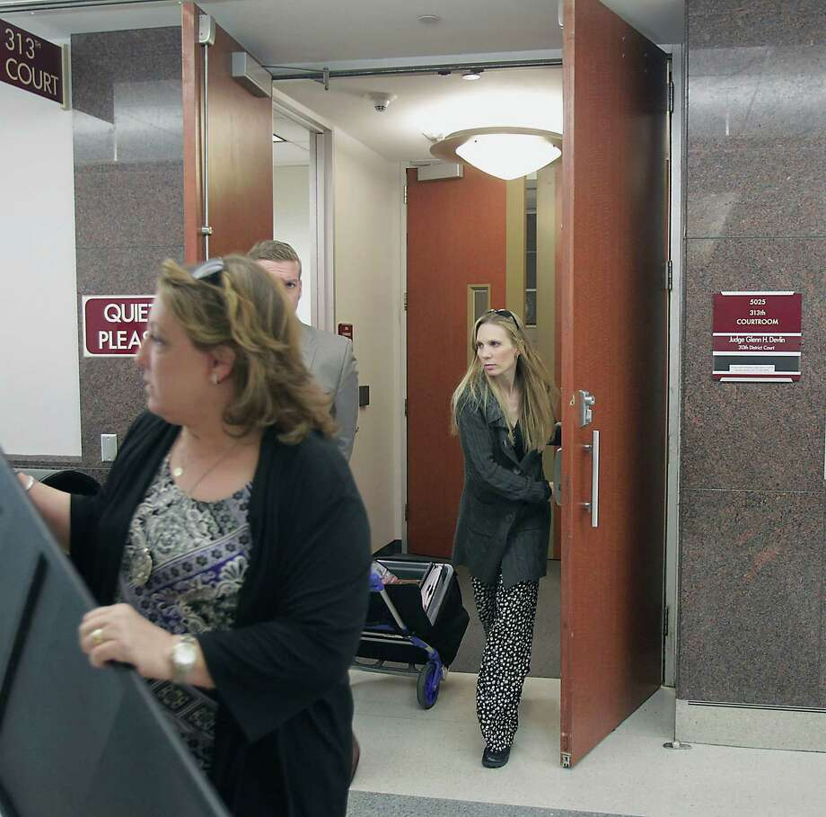 Tami Bleimeyer, right, leaves court Tuesday after a judge ruled that her six children should have no contact with her. She also testified that she is pregnant, with a baby due in August. Photo: James Nielsen, Staff / © 2014  Houston Chronicle