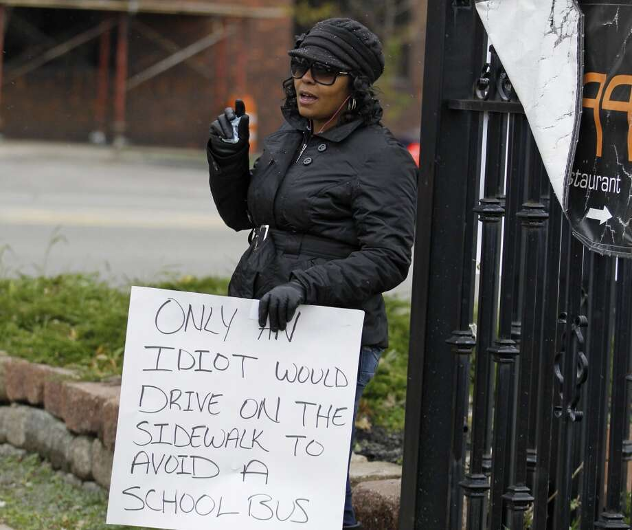 Shena Hardin holds up a sign to serve a highly public sentence Tuesday, Nov. 13, 2012, in Cleveland, for driving on a sidewalk to avoid a Cleveland school bus that was unloading children. A Cleveland Municipal Court judge ordered 32-year-old Hardin to serve the highly public sentence for one hour Tuesday and Wednesday. (AP Photo/Tony Dejak) Photo: Tony Dejak, Associated Press