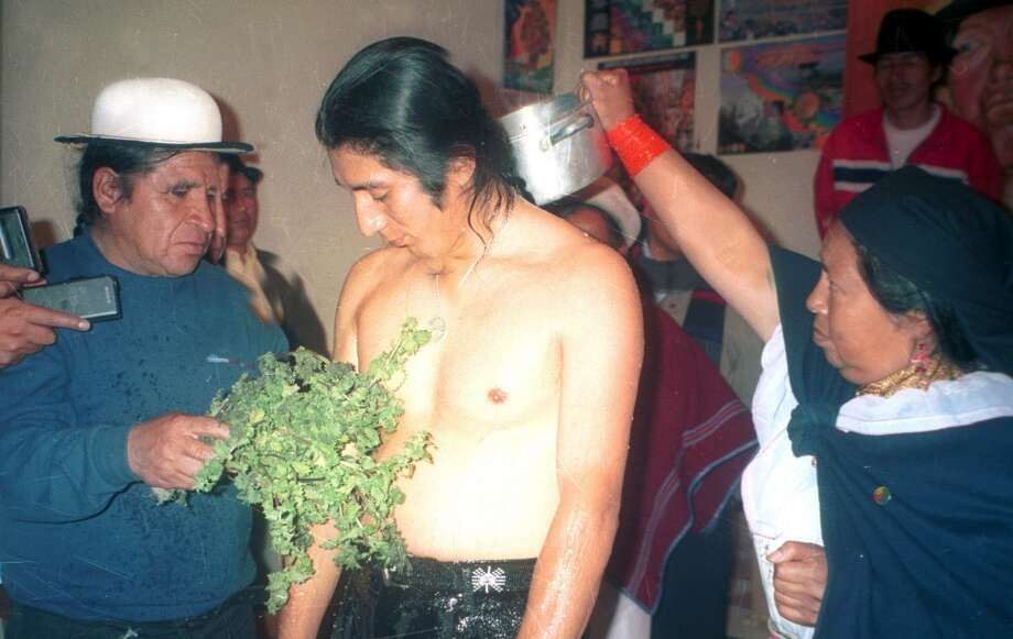 Fellow Pachakutik party members apply stinging nettles and cold water to Congressman Salvador Quishpe Friday, Aug. 15, 2003 for punishment after he didn't vote against a government-sponsored bill on wage reform. He left Congress before the vote, but the bill was soundly defeated even without him. Ecuador's judicial system allows indigenous communities to apply traditional punishments, and such public humiliation and beatings are common in isolated Andean villages. (AP Photo/Ecuarunari) Photo: AP