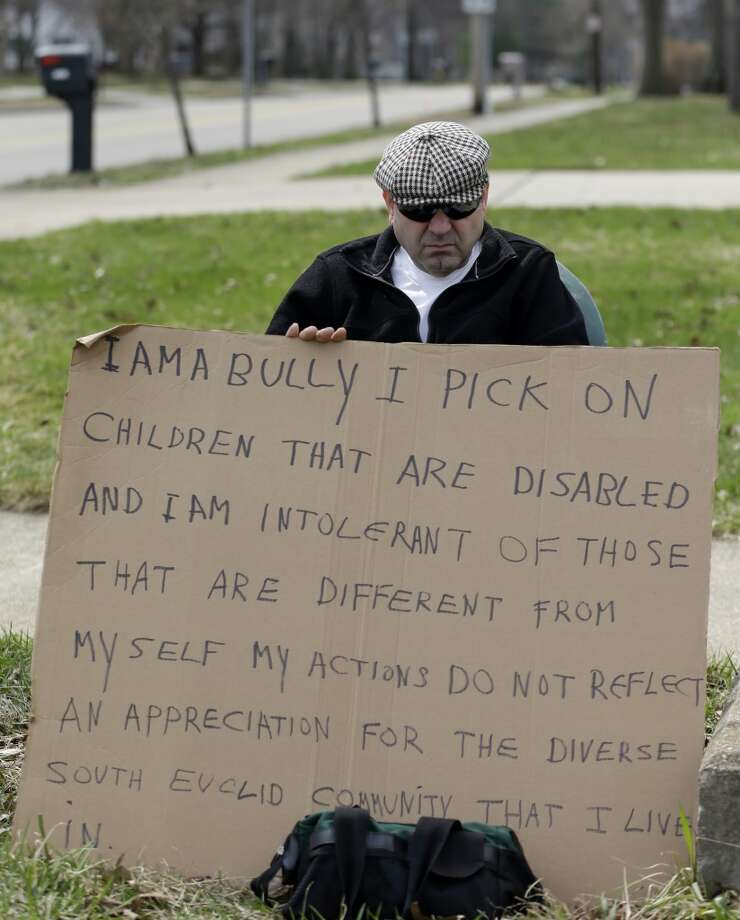 "Edmond Aviv sits on a street corner holding a sign Sunday, April 13, 2014, in South Euclid, Ohio declaring he's a bully, a requirement of his sentence because he was accused of harassing a neighbor and her disabled children for the past 15 years.  Municipal Court Judge Gayle Williams-Byers ordered Aviv, 62,  to display the sign for five hours Sunday. It says: ""I AM A BULLY! I pick on children that are disabled, and I am intolerant of those that are different from myself. My actions do not reflect an appreciation for the diverse South Euclid community that I live in."" (AP Photo/Tony Dejak) Photo: Tony Dejak, Associated Press"