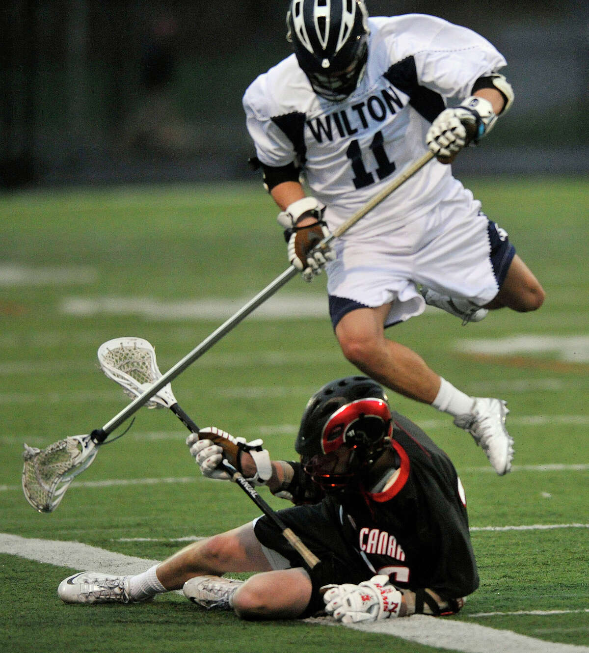 Wilton's Michael Brown leaps over New Canaan's Peter Swindell during their lacrosse game at Wilton High School in Wilton, Conn., on Tuesday, April 15, 2014.