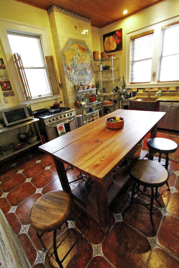 Jerry Lockey built the island/bar in the kitchen and installed the tile mural from Mexico on the wall. A painting by Elizabeth Rodriguez is above the corner shelves. Lockey calls the kitchen industrial Tuscan. Open shelves make everything visible and easy for him to reach. Photo: Danny Warner, For The Express-News