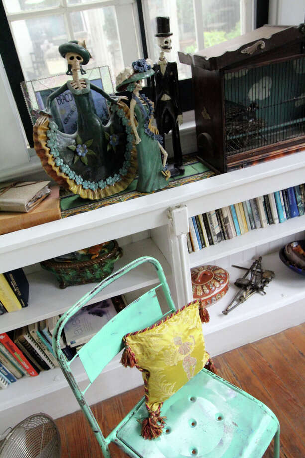 Mexican Catrina dolls top a built-in bookshelf in the sunroom. Photo: Danny Warner, For The Express-News