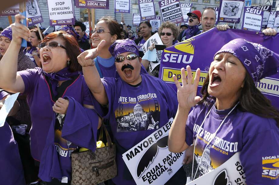 (l to r) Rosalina David, Shawn Campos and Elenor Collemarcine all union workers at Laguna Honda hospital join union workers and supporters as they rally in front of City Hall, on Tuesday April 15, 2014, in San Francisco, Calif. City nurses, janitors and other workers rally in front of city hall to protest the tax breaks that that local high-tech companies are receiving as they move into the Market Street area. Photo: Michael Macor, The Chronicle