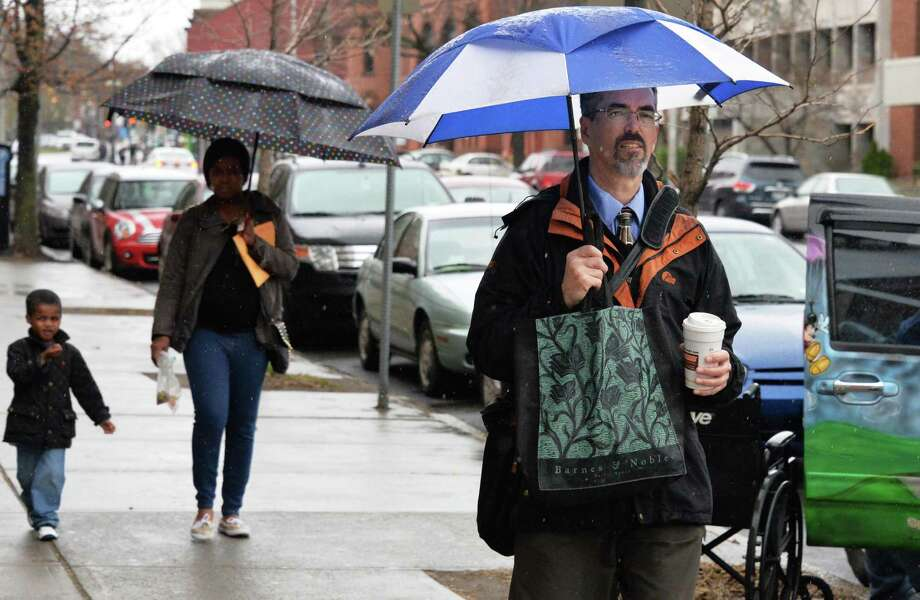 Dave Morrill, right, of Voorheesville makes his way along Washington Avenue in a light rain Tuesday April 15, 2014, in Albany, NY.  Morrill is less concerned with today's rain than tommorrow's predicted cold weather.  (John Carl D'Annibale / Times Union) Photo: John Carl D'Annibale